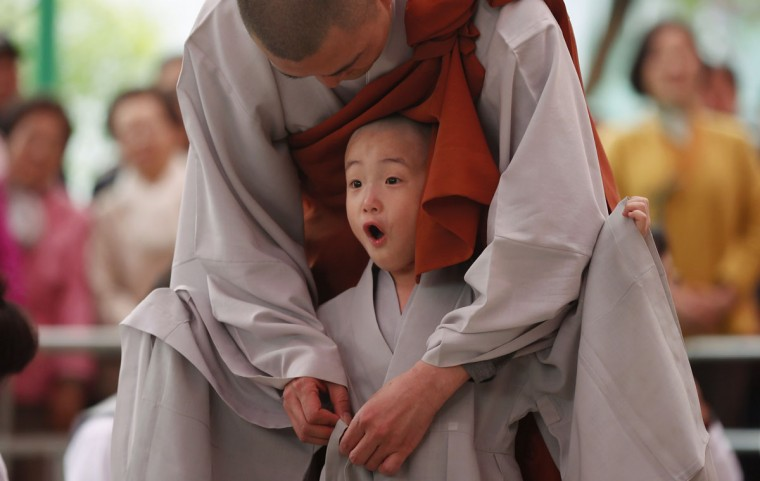 A novice monk reacts after getting his head shaved during an event to celebrate the upcoming birthday of Buddha at Jogye temple in Seoul, South Korea. (Kim Hong-Ji/Reuters)