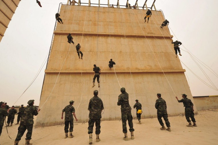 """Soldiers rappel down a wall during a military graduation parade for trainees from the Libyan Army """"Thunderbolt"""" Special Forces unit, in Benghazi . The trainees form the first batch of graduates which enlisted after the 2011 Libyan revolution. (Esam Al-Fetori /Reuters photo)"""