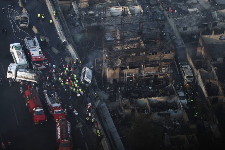 Firefighters and rescue workers stand amidst the rubble of destroyed houses after the explosion of a gas tanker truck in San Pedro Xalostoc, on the outskirts of Mexico City. A gas tanker truck exploded on a highway north of Mexico City, killing at least 20 people and injuring 36 others as a fireball tore through cars and homes. (Reuters photo)
