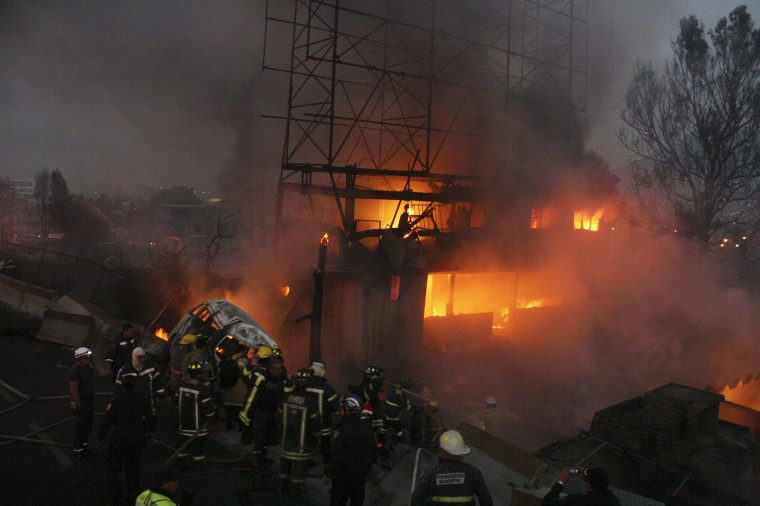 Firefighters try to extinguish a fire caused by the explosion of a gas tanker truck in San Pedro Xalostoc, on the outskirts of Mexico City. A gas tanker truck exploded on a highway north of Mexico City, killing at least 20 people and injuring 36 others as a fireball tore through cars and homes. (Reuters photo)