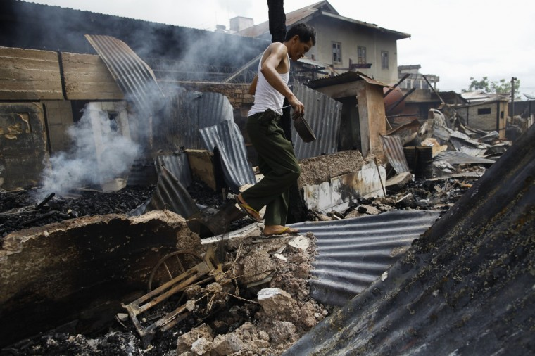 A soldier walks among debris after a riot between Muslims and Buddhists in Lashio township. Security forces struggled to control Buddhist mobs who burned Muslim homes for a second day in the northern Myanmar city of Lashio in a dangerous widening of ultra-nationalist Buddhist violence. (Soe Zeya Tun/Reuters photo)