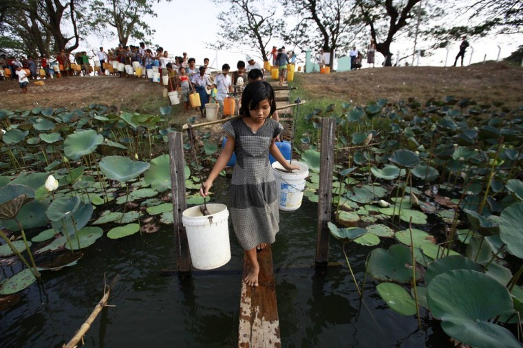 People line up to collect water at Yazarthingyan lake in Dala township, near Yangon May 12, 2013. Dala township is located near the sea and the only source of freshwater is from the inland lakes which have all dried up, with the exception of Yazarthingyan lake. According to the local authorities, the lake is only opened to locals once every three days, with over 1,000 people lining up to collect water when the authorities opened the lake from 4 pm to 5 pm. (Soe Zeya Tun/Reuters)