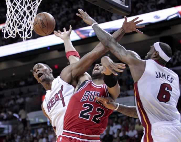 Chicago Bulls power forward Taj Gibson (22) is fouled as he goes to the basket between Miami Heat small forward LeBron James (6) and center Chris Bosh (1) during Game 1 of their NBA Eastern Conference semi-final basketball playoff in Miami, Florida. (Joe Skipper/Reuters photo)