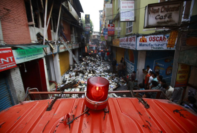 A fire engine stands by at a narrow street outside the houses that caught fire at Thamel, a major tourist hub in Kathmandu, Nepal. According to local media, the fire started in the kitchen of Faces Lounge and Bar after a cooking gas cylinder exploded and spread to two neighboring buildings, including a major book store. (Navesh Chitrakar/Reuters)