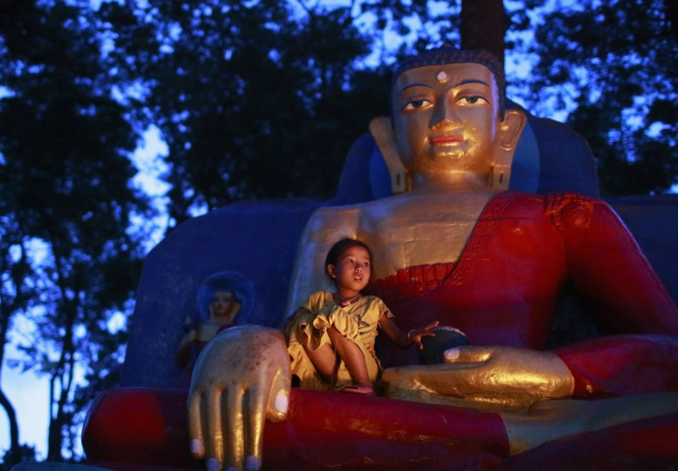 """A girl sits on an idol of Lord Buddha during the Buddhist festival locally called """"Saka Dawa"""" in Kathmandu, Nepal. The 15-day festival is celebrated following the birthday of Lord Buddha, in which Buddhist devotees circumambulate the stupa 13 times and light lamps. (Navesh Chitrakar/Reuters)"""