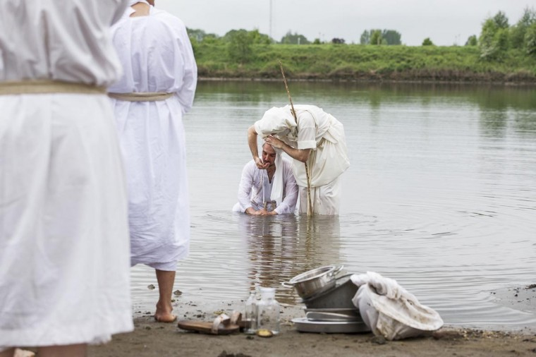 A priest (R) splashes water at a believer during a baptising ceremony for Mandaen followers at the Lek River near Houten May 20, 2013. May 20 is a holy day for the Mandaeans all over the world as followers cleanse themselves by being baptised in a river of choice. (Michael Kooren/Reuters)