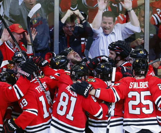 Chicago Blackhawks defenseman Brent Seabrook (C) lets out a scream while being mobbed by teammates after scoring an overtime goal to defeat the Detroit Red Wings and win Game 7 of their NHL Western Conference semi-final hockey playoff in Chicago, Illinois. (Jeff Haynes/Reuters photo)