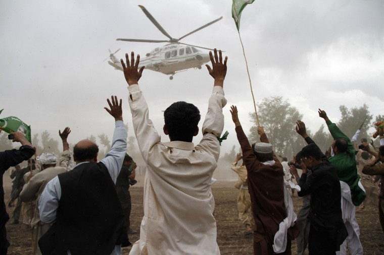 Supporters wave towards a helicopter transporting Nawaz Sharif, leader of political party Pakistan Muslim League-Nawaz (PML-N), as he leaves after his election campaign rally in Peshawar. Pakistan's general elections will be held on May 11. (Fayaz Aziz/Reuters photo)