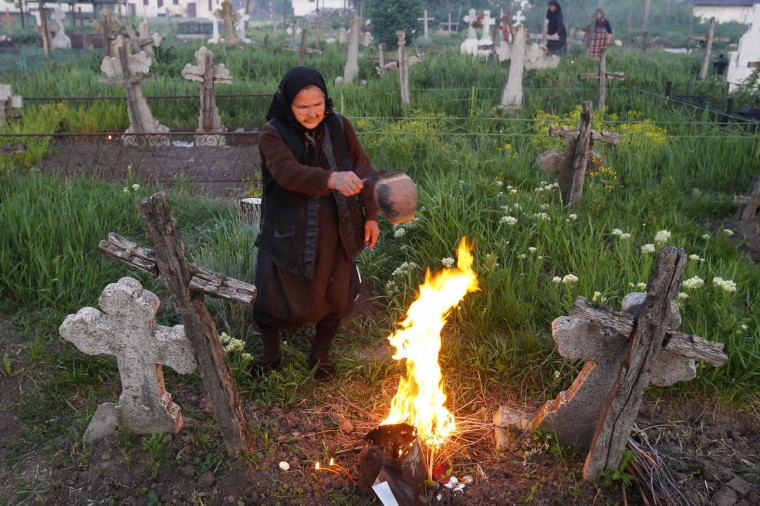 A woman burns incense in front of the graves of her relatives at a cemetery in the village of Copaciu, 42 km (26 miles) southwest of Bucharest, early morning. Orthodox women went to church and cemeteries in the early morning to light candles, burn incense and mourn their dead relatives as part of a southern Romania tradition. Holy Thursday, is the day Christians commemorate the Last Supper of Jesus Christ. Romania's Orthodox majority celebrates Easter on May 5. (Bogdan Cristel/Reuters photo)