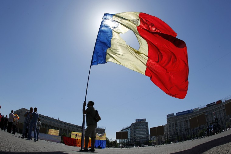 A man holds Romania's national flag during a Labour Day rally in front of Victoria palace, Romania's government headquarters, in downtown Bucharest. (Bogdan Cristel/Reuters)