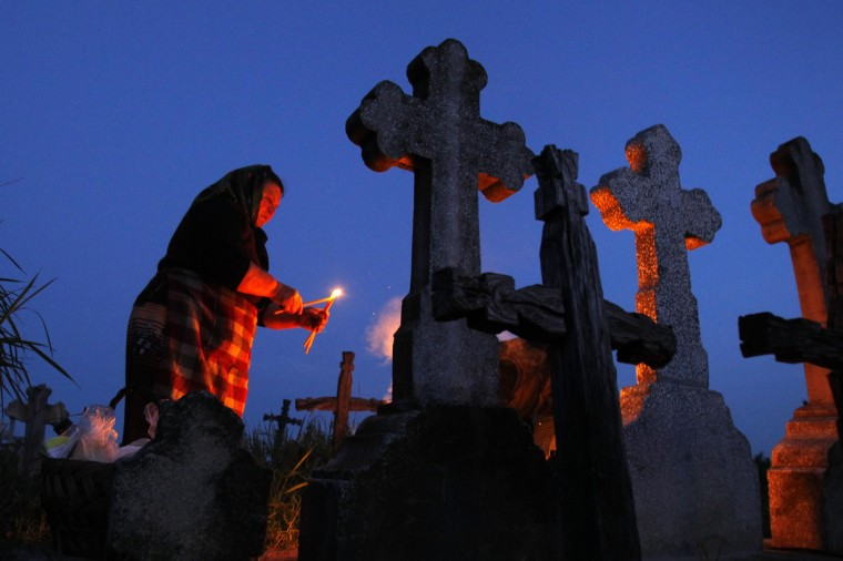 A woman lights candles in front of the graves of her relatives at a cemetery in the village of Copaciu, 42 km (26 miles) southwest of Bucharest, early morning. Orthodox women went to church and cemeteries to light candles, burn incense and mourn their dead relatives as part of a southern Romania tradition. Holy Thursday is the day Christians commemorate the Last Supper of Jesus Christ. Romania's Orthodox majority celebrates Easter on May 5. (Bogdan Cristel/Reuters photo)
