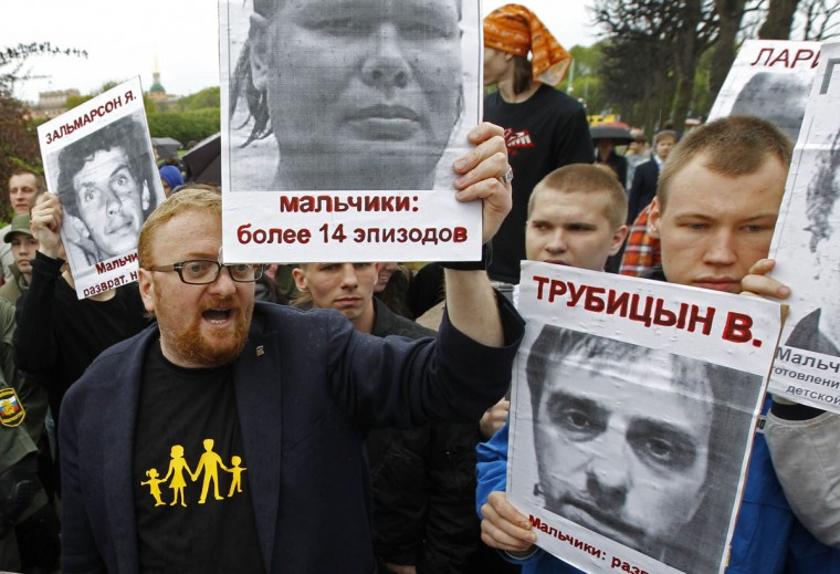 """United Russia deputy Vitaly Milonov (L) and gay rights opponents hold portraits of convicted paedophiles during a rally to mark International Day Against Homophobia and Transphobia in St. Petersburg, Russia. The words on the portrait Milonov is holding reads, """"Young boys: More than 14 incidents."""" (Alexander Demianchuk/Reuters)"""