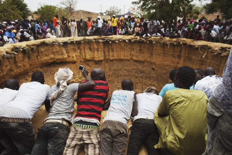 People watch a traditional ceremony taking place in a large former well in the village of Ndande, Senegal. Every year, inhabitants of the village take part in a Sufi Muslim ceremony called Gamou-Ndande. The ceremony combines nights of praying and chanting as well as traditionally animist ceremonies. The well, called Kalom, was the site of historic battles in Senegalese history. According to local historian Baye Niass, the well dates back to the 16th century. Today there is no water in the former well and it is used for ceremonial purposes. Niass says the well measure 36 meters in depth an 11m in diameter. (Joe Penney/Reuters)