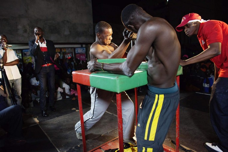 "Arm wrestlers Mamadou Ba (L) and Cheikh Faye battle each other during a competition in the crowded Medina district of Dakar, Senegal, May 13, 2013. The ""Jaay Doole,"" which translated from Wolof means ""Show Your Strength"", is a competition that aims to find the best arm wrestler in Senegal by holding tournaments throughout the country. (Joe Penney/Reuters)"