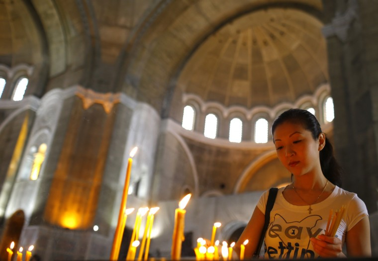 A worshipper lights candles as she prays during Good Friday at the St. Sava temple in Belgrade. Serbia and other Eastern Orthodox countries celebrate Easter this weekend. (Marko Djurica/Reuters photo)