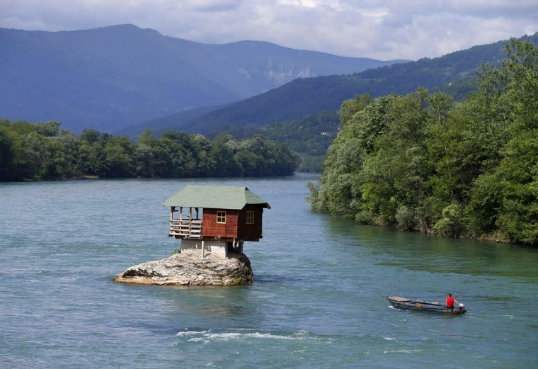 A man rows a boat near a house built on a rock on the river Drina near the western Serbian town of Bajina Basta, about 160km (99 miles) from the capital Belgrade. The house was built in 1968 by a group of young men who decided that the rock on the river was an ideal place for a tiny shelter, according to the house's co-owner, who was among those involved in its construction. (Marko Djurica/Reuters)