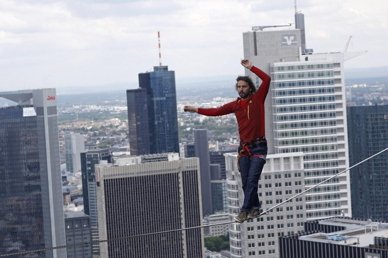 Professional slackliner Reinhard Kleindl walks a high wire in front of the Frankfurt skyline May 25, 2013. Austrian Kleindl set a world record on Saturday by walking the highest urban high line at 607 ft. (Ralph Orlowski/Reuters)