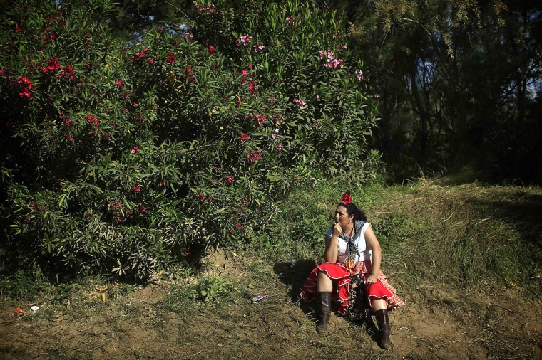 A pilgrim makes a stop after crossing the Quema river on her way to the shrine of El Rocio in the province of Seville, southern Spain. Every spring hundreds of thousands of devotees converge at a shrine to pay homage to the Virgin del Rocio during an annual pilgrimage which combines religious fervor and festive color. (Marcelo del Pozo/Reuters photo)
