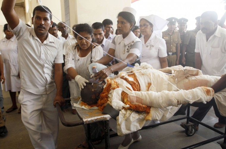 Sri Lankan Buddhist monk Bowatte Indaratane Thera is tended by medical personnel as he is carried into a hospital on a stretcher in Colombo May 24, 2013. According to local media, the monk had set himself on fire in a form of protest against the slaughter of cattle slaughter. (Stringer/Reuters)