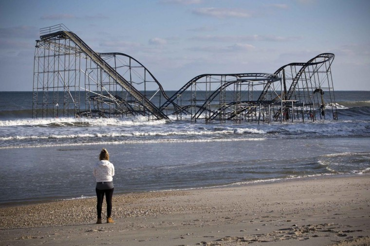 A woman looks at a roller coaster sitting in the ocean, when the boardwalk it was built upon collapsed during Hurricane Sandy, in Seaside Heights, New Jersey November 28, 2012. (Andrew Burton/Reuters)