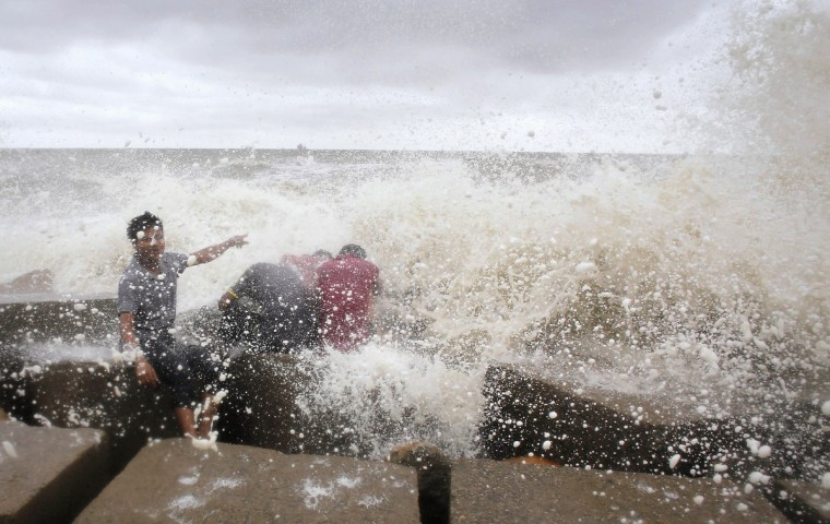 Waves crash into people sitting by the shore of the Bay of Bengal before cyclone Mahasen approaches in Chittagong. Mahasen started crossing Bangladesh's low-lying coast on Thursday, bearing down on the ports of Chittagong and Cox's Bazar, as tens of thousands of people huddled in shelters from a storm which the United Nations says threatens 4.1 million people. (Andrew Biraj/Reuters photo)