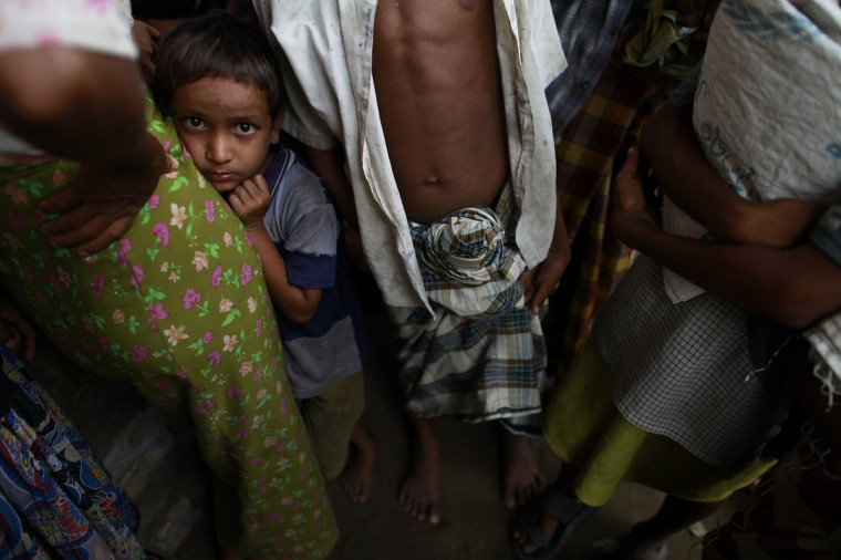 A boy from a Rohingya internally displaced persons (IDP) camp looks up as he huddles next to his mother while queuing for food in a school, where they were evacuated to shelter from cyclone Mahasen when it landed, outside of Sittwe, Myanmar. (Soe Zeya Tun/Reuters)