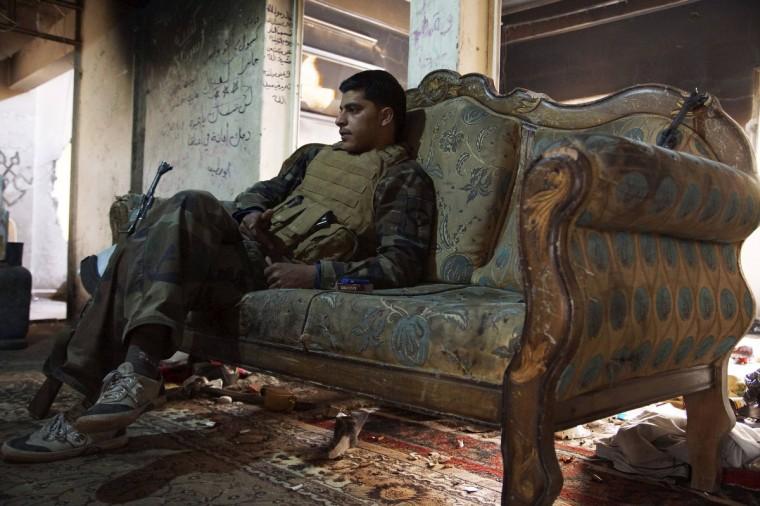 A Free Syrian Army fighter sits on a sofa inside a house in Deir al-Zor . (Khalil Ashawi/Reuters)