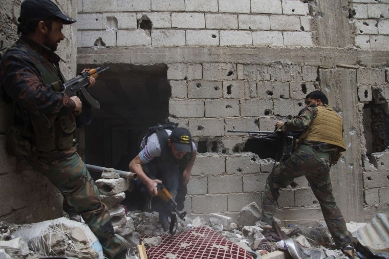 Free Syrian Army fighters lay cover fire after what they say was during clashes with forces loyal to President Bashar al-Assad in Deir al-Zor.(Khalil Ashawi/Reuters)