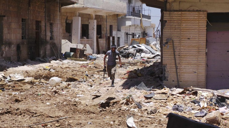 A Free Syrian Army fighter carrying his weapon walks along a street piled with rubble near damaged buildings in Deraa.