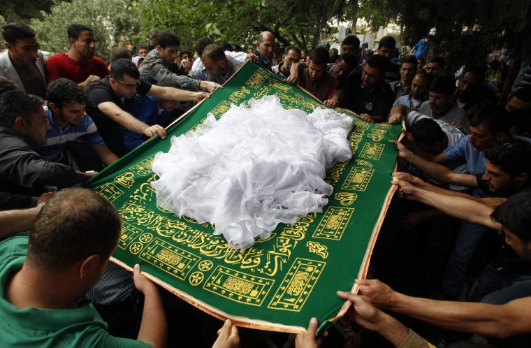 Relatives cover the body of 22-year-old Ayten Calim with a Muslim prayer rug and her wedding dress as they lower her into a grave in the town of Reyhanli in Hatay province near the Turkish-Syrian border. Calim was one of around 50 people to have been killed by two bomb attacks in Reyhanli over the weekend. (Umit Bektas/Reuters)