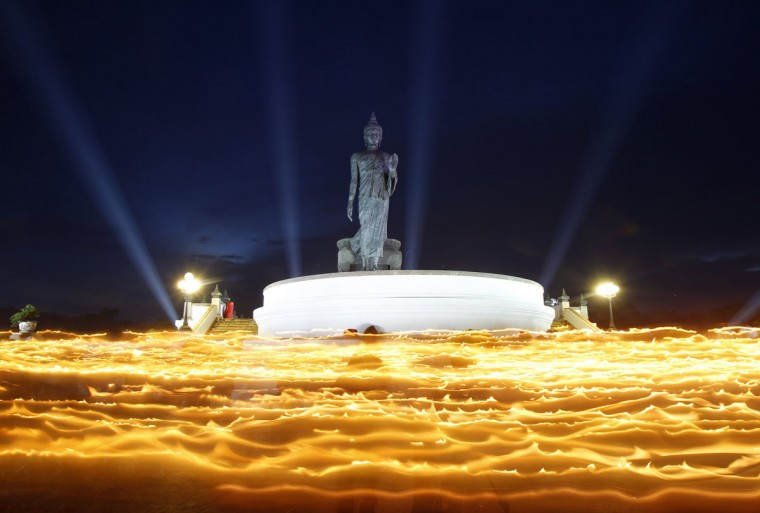 Buddhists carry candles while encircling a large Buddha statue during Vesak Day, an annual celebration of Buddha's birth, enlightenment and death, at a temple in Nakhon Pathom province on the outskirts of Bangkok, Thailand. Picture taken using long exposure. (Chaiwat Subprasom/Reuters)