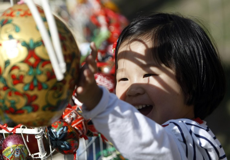 A child plays with an installation made of painted wooden eggs, attributes of the Orthodox Easter, in central Kiev. Orthodox believers will celebrate Easter on May 5. (Sergii Polezhaka/Reuters photo)