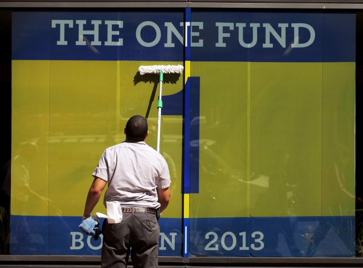 """A worker cleans a window displaying a banner for """"The One Fund, Boston"""" , the name of the fund for the victims of the Boston Marathon bombings, in Boston, Massachusetts. (Brian Snyder/Reuters photo)"""