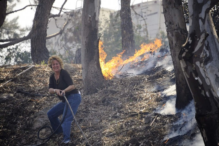 A resident pulls a hose line to attempt to stop flames from spreading down the hillside as The Springs Fire pushes towards the coast near Camarillo, California May 2, 2013. (Gene Blevins/Reuters)