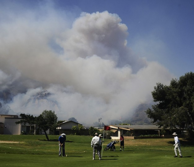 Golfers continue to play as smoke (background) billows from a raging wildfire pushing towards the coast in Camarillo May 2, 2013. (Gene Blevins/Reuters)