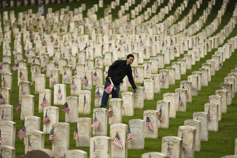 "A man places a flag at a grave at Cypress Hills National Cemetery in Brooklyn, New York May 25, 2013. The annual ""Flags-In"" ceremony is held ahead of Memorial Day to honor the nation's fallen members of the military. Flags will be placed at more than 220,000 graves. (Eduardo Munoz/Reuters)"