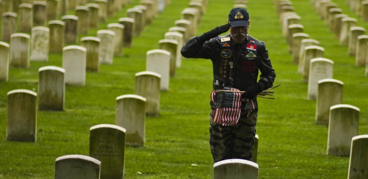 "Carlos Varon pays respect to war fallen soldiers while he places flags at graves at Cypress Hills National Cemetery in Brooklyn, New York May 25, 2013. The annual ""Flags-In"" ceremony is held ahead of Memorial Day to honor the nation's fallen members of the military. Flags will be placed at more than 220,000 graves. (Eduardo Munoz/Reuters)"
