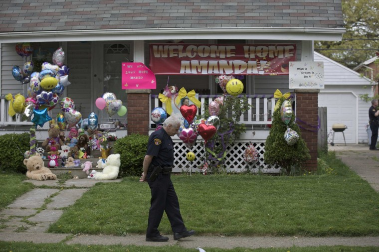 A Cleveland police officer is present outside the home of Amanda Berry's sister in Cleveland, Ohio. Amanda Berry, free less than two days from a decade of captivity with two other women in a Cleveland house, arrived on Wednesday at her sister's home, where her family pleaded for privacy. (John Gress/Reuters)