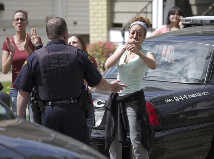 Neighbors react as Amanda Berry arrives at her sister's home in Cleveland, Ohio. Berry, Gina DeJesus, Michelle Knight and Berry's 6-year-old daughter escaped a Cleveland home where they were held captive. Berry, now 27, was found with her daughter, conceived and born during her captivity, along with DeJesus, 23, who vanished aged 14 in 2004, and Knight, 32, who was 20 when she went missing in 2002. (John Gress/Reuters)