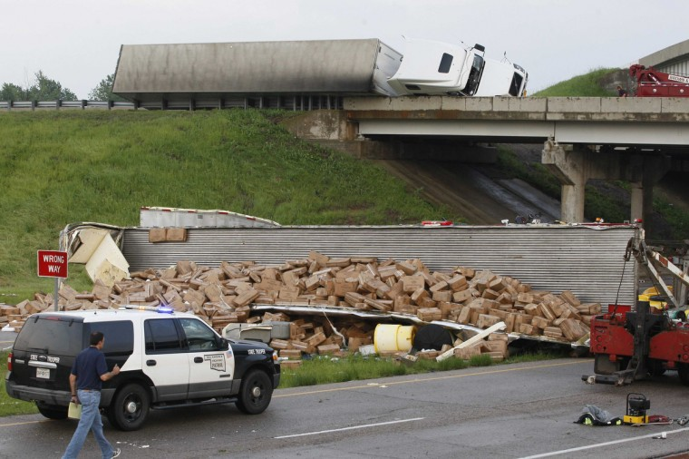 A semi-tractor trailer (top) rests on its side against the guard rails on Interstate 40 as another trailer lies broken open on the road below after falling from I-40, following a tornado strike near Highway 177 north of Shawnee, Oklahoma. (Bill Waugh/Reuters photo)