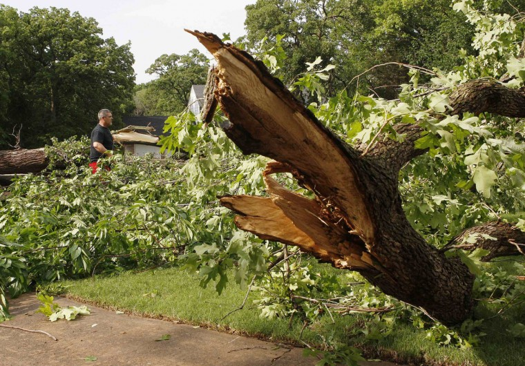 Bob Cameron of Edmond, Oklahoma, helps a neighbor move downed trees after a tornado swept through the eastern part of Edmond, Oklahoma. (Bill Waugh/Reuters photo)