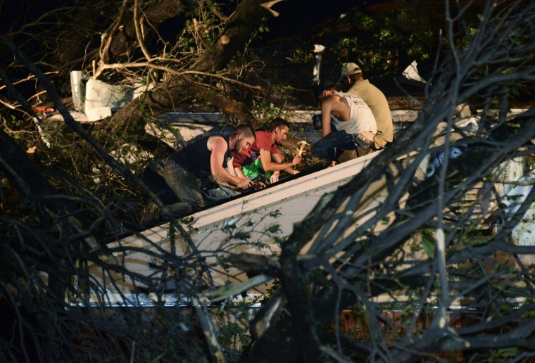 Residents help repair the roof of their neighbor's house which was damaged by a fallen tree when a tornado swept through Shawnee, in Oklahoma. (Gene Blevins/Reuters photo)