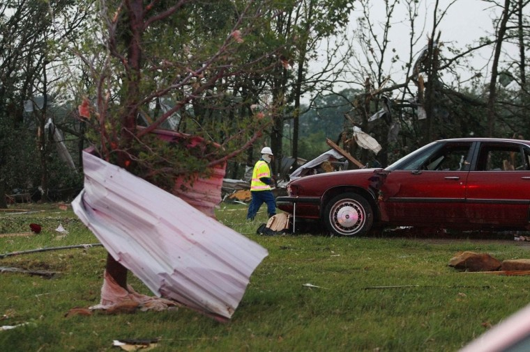 An official walks next to storm debris at a mobile home park which was destroyed by a tornado on Sunday, west of Shawnee, Oklahoma. (Bill Waugh/Reuters photo)