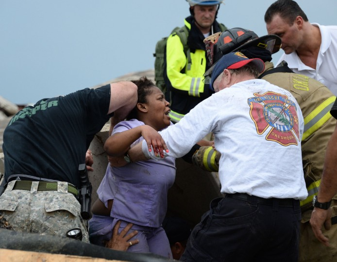 Rescue workers help free one of the 15 people that were trap at a medical building at the Moore hospital complex after a tornado tore through the area of Moore, Oklahoma May 20, 2013. (Gene Blevins/Reuters)