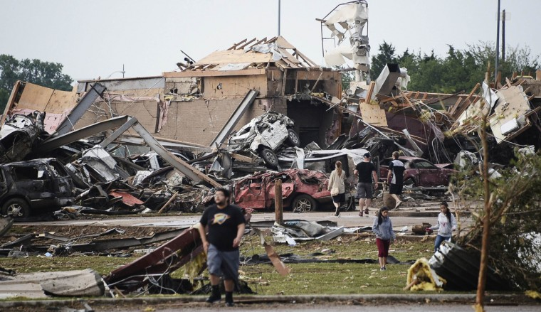 People walk near destroyed buildings and vehicles after a tornado struck Moore, Oklahoma, near Oklahoma City, May 20, 2013. At least 91 people, including 20 children, were feared killed when a 2 mile wide tornado tore through the Oklahoma City suburb of Moore, trapping victims beneath the rubble as one elementary school took a direct hit and another was destroyed. (Gene Blevins/Reuters)