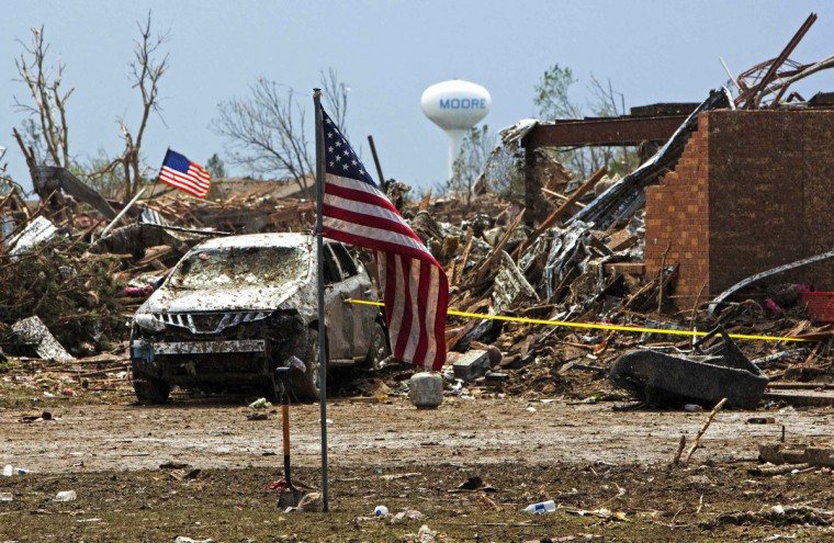 American flags wave over the remains of Plaza Towers Elementary school in Moore, Oklahoma May 21, 2013 after it was destroyed by a massive tornado May 20. Emergency workers pulled more than 100 survivors from the rubble of homes, schools and a hospital in an Oklahoma town hit by a powerful tornado, and officials lowered the death toll from the storm to 24, including nine children. (Richard Rowe/Reuters)