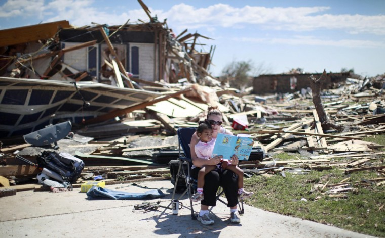 Sarah Dick reads a Doctor Suess book to her three-year-old daughter Jadyn at the driveway of her tornado-destroyed house in Oklahoma City, Oklahoma. Rescue workers with sniffer dogs picked through the ruins on Wednesday to ensure no survivors remained buried after a deadly tornado left thousands homeless and trying to salvage what was left of their belongings. (Rick Wilking/Reuters)