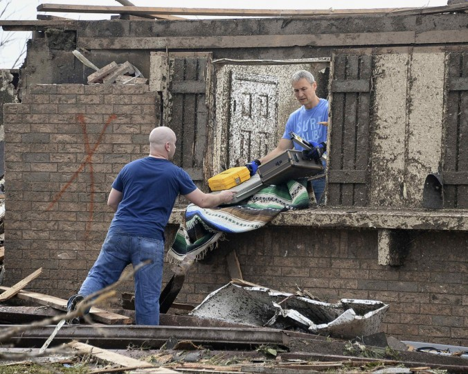 People salvage belongings after a huge tornado struck Moore, Oklahoma May 20, 2013. A 2-mile-wide (3-km-wide) tornado tore through the Oklahoma City suburb of Moore on Monday, killing at least 51 people while destroying entire tracts of homes, piling cars atop one another, and trapping two dozen school children beneath rubble. (Gene Blevins/Reuters)