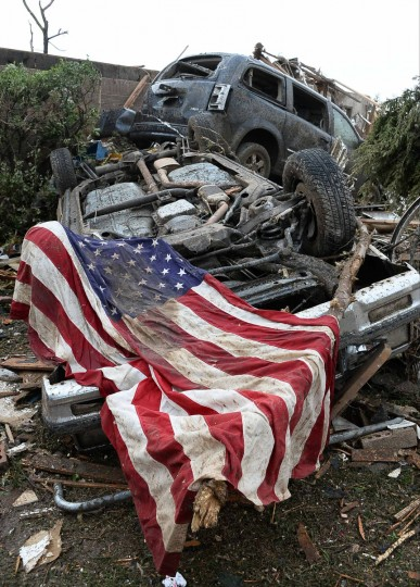 An American flag lies on top of an overturned car after a tornado struck Moore, Oklahoma, May 20, 2013. A 2-mile-wide (3-km-wide) tornado tore through the Oklahoma City suburb of Moore on Monday. (Gene Blevins/Reuters)