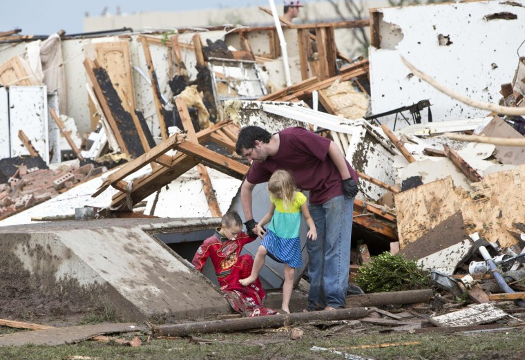 A man and two children walk through debris after a huge tornado struck Moore, Oklahoma, near Oklahoma City, May 20, 2013. A massive tornado tore through the Oklahoma City suburb of Moore on Monday, killing at least 51 people as winds of up to 200 miles per hour (320 kph) flattened entire tracts of homes, two schools and a hospital, leaving a wake of tangled wreckage. (Richard Rowe/Reuters)